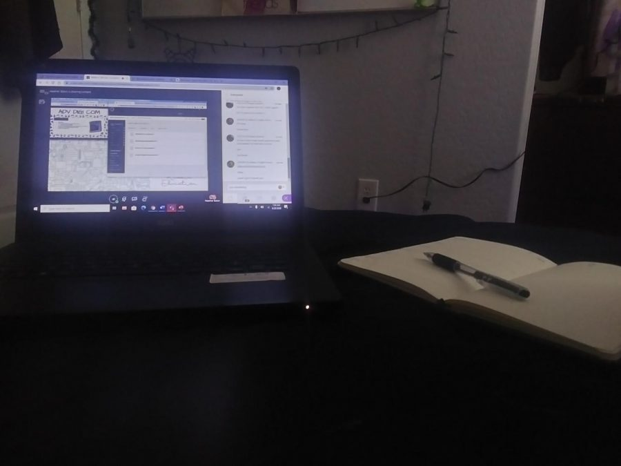 Laptop and notebook placed side by side on a bed.