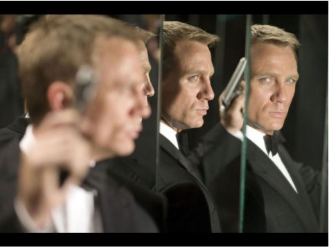 A picture of a man in a Black suite holding a gun standing in front of mirrors giving the allusion that there are three of him.