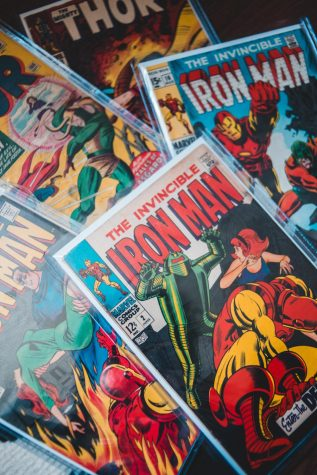 Image is a stack of Marvel comics, such as Iron Man and Thor.