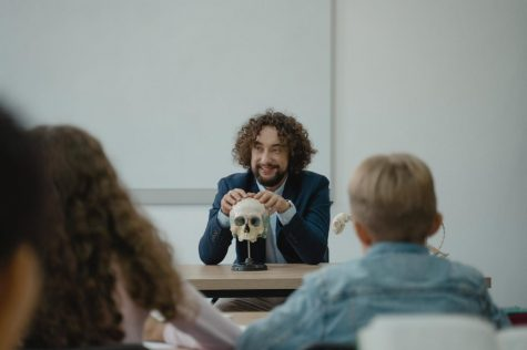 In this picture it shows a teacher teaching his students about the human skull.