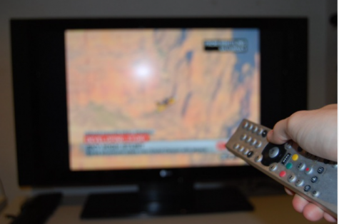 A tv turn on in the background, in the foreground the remote