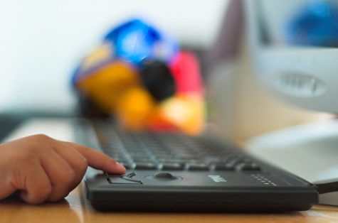 Person touching computer keyboard with index finger