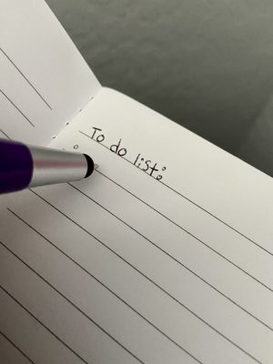 """A pen meeting a piece of paper with the words """"to do list"""" written at the top."""