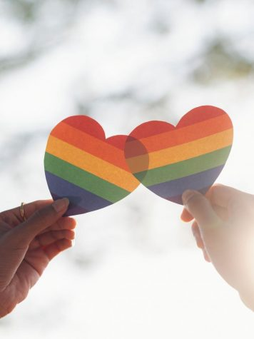 Two Hands holding Rainbow Colored Hearts